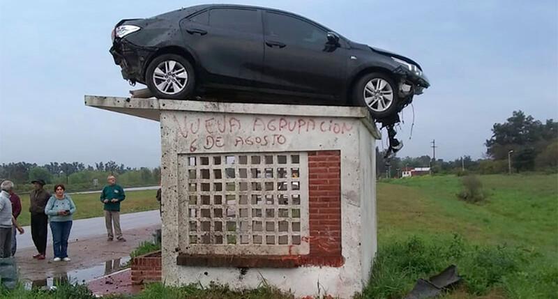 Un Toyota Corolla choca, vuelca y queda en el techo de una parada de transporte público