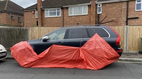 Carros estacionados en la calle son protegidos con lonas en una ciudad de Inglaterra