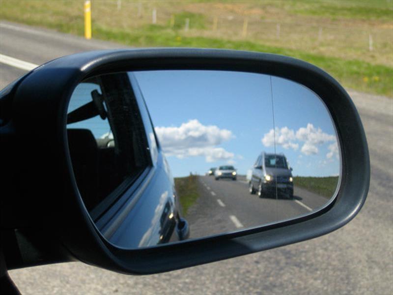 ¿A qué se debe que los objetos en el espejo derecho del automóvil están más cerca de lo que parece?